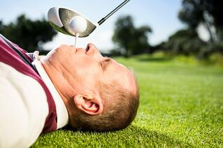 Golfer holding tee in his teeth on a sunny day at the golf course.jpeg